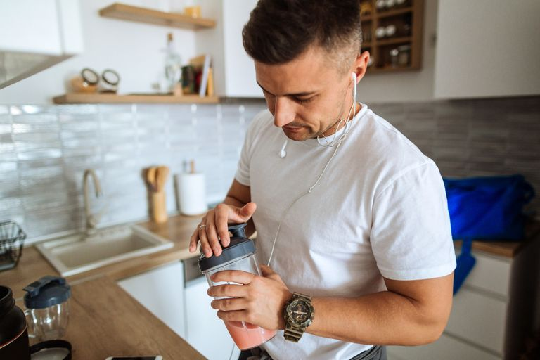young-man-making-protein-shake-before-training-royalty-free-image-1094095844-1557159032