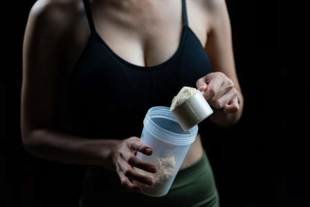 155944449-close-up-of-women-with-measuring-scoop-of-whey-protein-and-shaker-bottle-preparing-protein-shake-